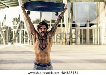 Young skater with tattoos holding longboard outside with back su Stock photo © DisobeyArt