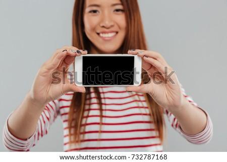 sevimli · genç · bayan · göstermek · cep · telefonu - stok fotoğraf © deandrobot