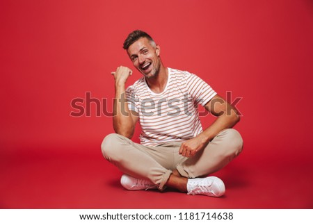 Image of brunette guy 30s in striped t-shirt smiling, while sitt Stock photo © deandrobot