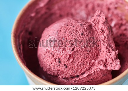 macro photo of scoop of frozen berry ice cream in a paper glass on a blue background top view stock photo © artjazz