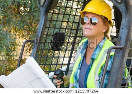 smiling female worker holding technical blueprints using small b stock photo © feverpitch