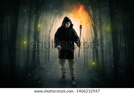 Man coming from dark forest with burning flambeau in his hand concept Stock photo © ra2studio