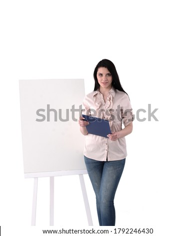 a young girl stands near a board with stickers and holds a pen and a tablet with sheets stock photo © traimak