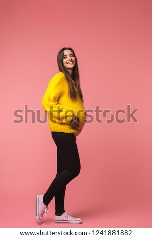 Young woman posing isolated over pink background looking aside. Stock photo © deandrobot