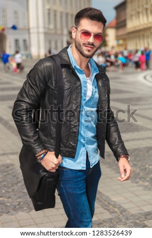 attractive young man holding shoulder bag walking through the ci Stock photo © feedough