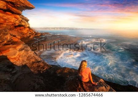 Female on rocks watching the ocean cascade around coastal rocks Stock photo © lovleah