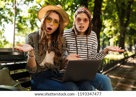 Confused displeased ladies friends outdoors sitting using laptop computer. Stock photo © deandrobot