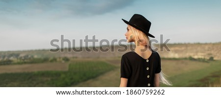 Photo of young woman 20s wearing black dress and hat photographi Stock photo © deandrobot