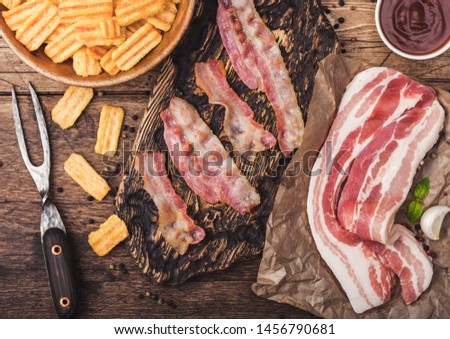 Bacon flavored snacks chips with grilled bacon rashers on vintage chopping board with smoked raw bac Stock photo © DenisMArt