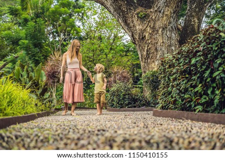 mother and son walking on a textured cobble pavement reflexology pebble stones on the pavement for stock photo © galitskaya
