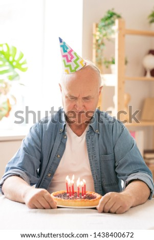 Retired man in birthday cap making wish in front of cake with candles Stock photo © pressmaster