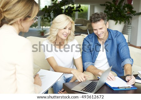 Mature woman consulting with real estate agent while her husband reading paper Stock photo © pressmaster