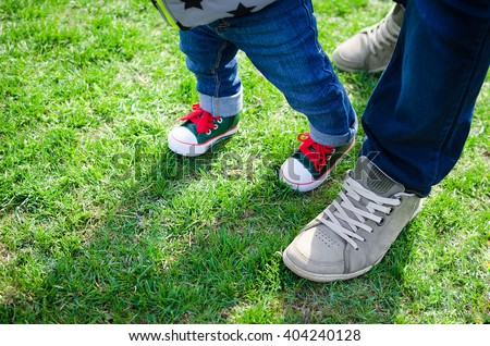 First steps concept - foot of father and son in stylish sneakers on the background of green grass. B Stock photo © galitskaya