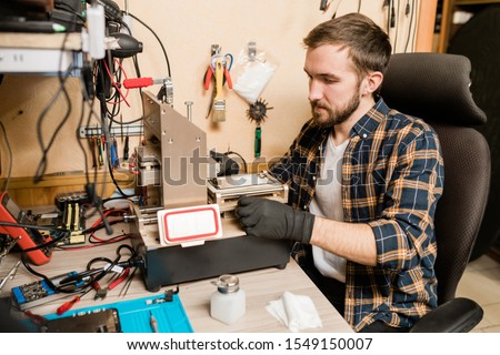 Bearded repairman in gloves trying to find out trouble of broken smartphone Stock photo © pressmaster
