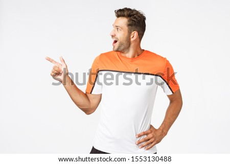 Excited, happy amused masculine sportsman in activewear, attend gym, pointing turning left astonishe Stock photo © benzoix