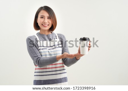 Young waitress of cafe in apron giving you glass of hot coffee in isolation Stock photo © pressmaster
