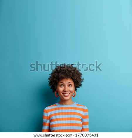 Vertical shot of pleased young Afro American woman feels relaxed and carefree, drinks aromatic coffe Stock photo © vkstudio