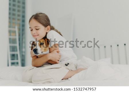 Pleased little girl plays with pet, embraces dog and keeps eyes closed from pleasure, dressed in nig Stock photo © vkstudio