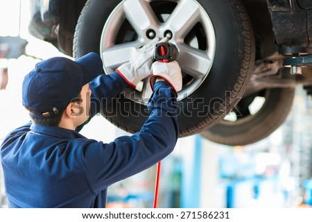 auto mechanic and man with tires at car shop Stock photo © dolgachov