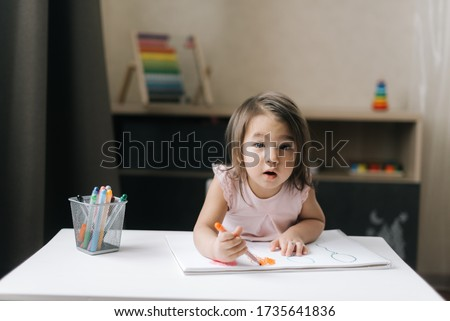 Cheerful little girl colouring at the table at home in kitchen Stock photo © Lopolo
