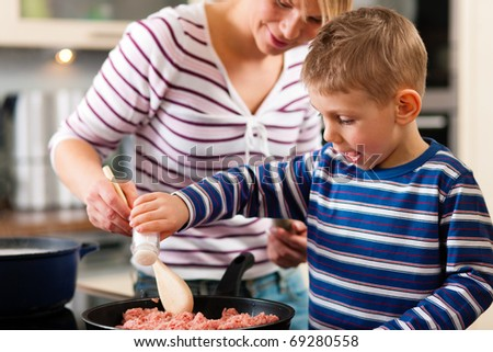 Family cooking in their kitchen - mother making some spaghetti s Stock photo © Lopolo
