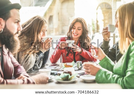 Photo of cheerful female drinks coffee with croissant, sits crossed legs with dreamful expression, h Stock photo © vkstudio