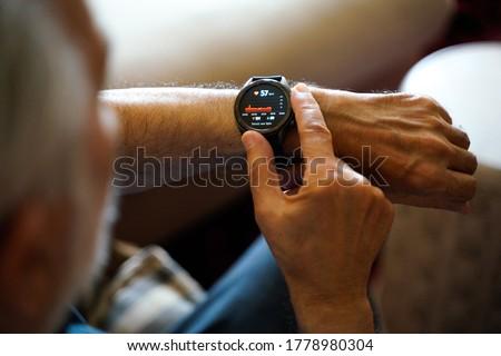 senior man checking time on his wristwatch Stock photo © dolgachov