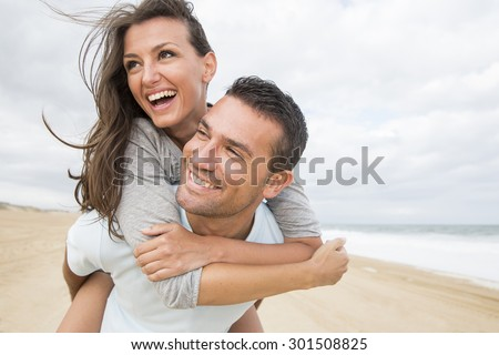 Portrait of young couple in love embracing at beach and enjoying Stock photo © HASLOO