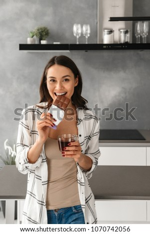 Attractive woman eating a chocolate bar while standing against a white background Stock photo © wavebreak_media