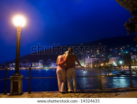 couple standing near the sea and looking at night city panoram stock photo © nejron