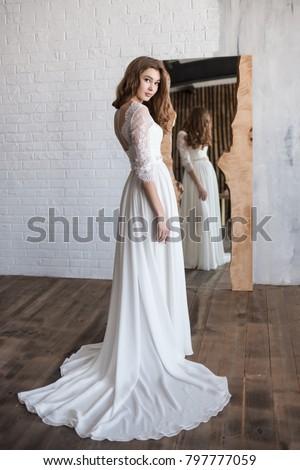 Stock photo: Beautiful bride woman posing in wedding dress isolated on gray b