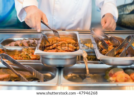 hand of cook takes nippers fried meat in lunch counter at public Stock photo © Paha_L