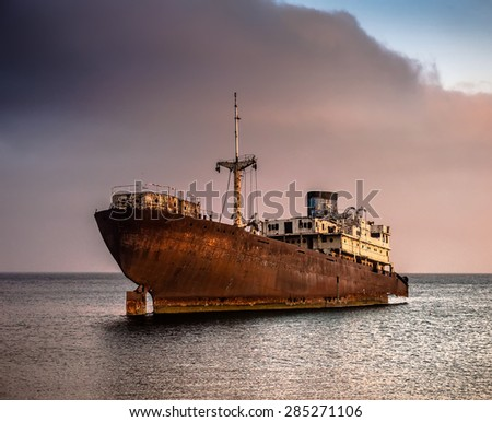 Old rusty Ship in the blue ocean at coast with cloud and green mountain background, Cape Verde islan Stock photo © attiarndt