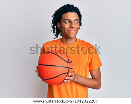 side view of african sporty man holding basketball ball on black Stock photo © LightFieldStudios