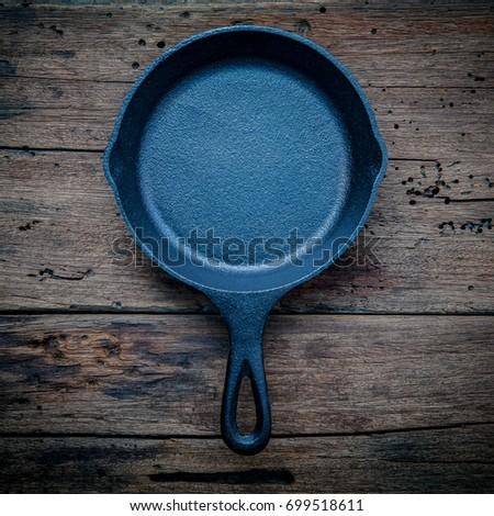 Empty cast-iron pan with cutlery on dark background for restaurant menu, top view Stock photo © yelenayemchuk