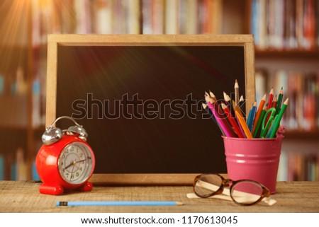 slate with desk organizer and alarm clock by eyeglasses against empty blackboard in school stock photo © wavebreak_media