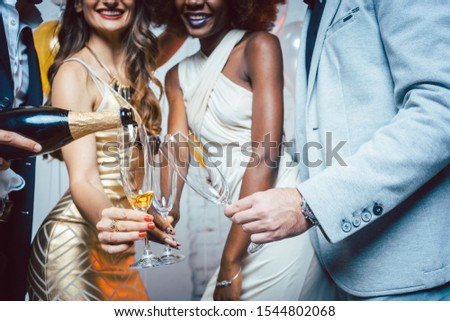 Man pouring sparkling wine into glass of his friends celebrating a party Stock photo © Kzenon