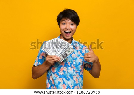 Pleased young asian man standing isolated over yellow background holding pizza smell. Stock photo © deandrobot
