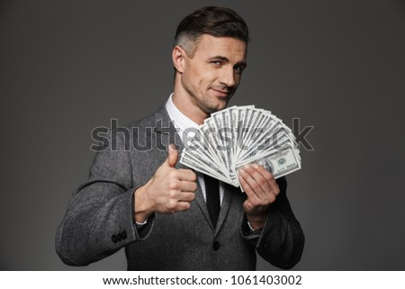 Image of successful businessman 30s in suit holding fan of money stock photo © deandrobot