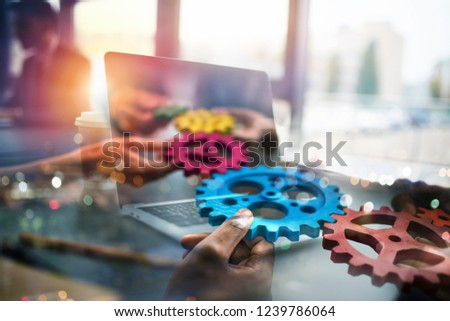 Business people with gears in hand that exit from a laptop. concept of remote cooperation and teamwo Stock photo © alphaspirit