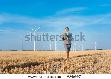 women putting money into an ethical investment of wind turbines stock photo © kzenon