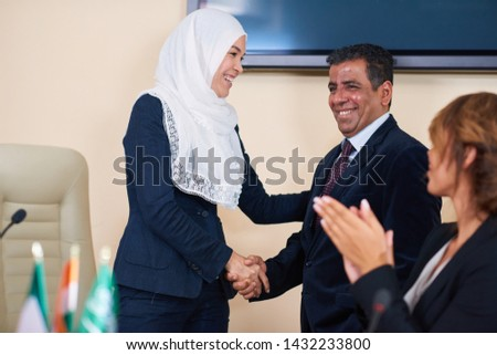 Happy young female delegate in hijab congratulating one of foreign speakers Stock photo © pressmaster