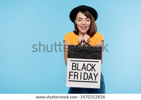 cute brunette girl in hat and t shirt holding black friday paperbag stock photo © pressmaster