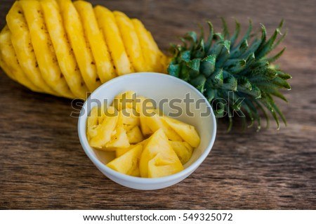 Pineapple slices and pineapple shelled Asian-style on the old wooden background. Tropical fruit conc Stock photo © galitskaya