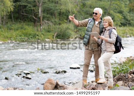 Happy mature backpacker showing his wife sights of their destination Stock photo © pressmaster