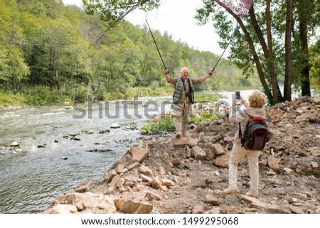 Ecstatic mature man lifting trekking sticks while his wife photographing him Stock photo © pressmaster