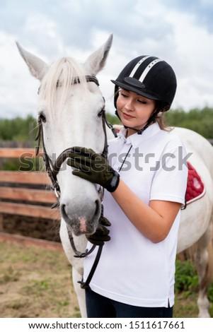Young active female cuddling muzzle of white purebred racehorse Stock photo © pressmaster