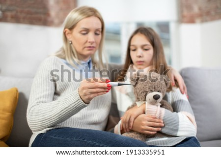 Hand of young mother holding thermometer after measuring temperature Stock photo © pressmaster