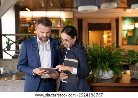 Young businesswoman scrolling through electronic form of contract in touchpad Stock photo © pressmaster