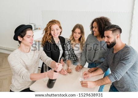 Group of young friends with flutes looking at guy opening bottle of champagne Stock photo © pressmaster